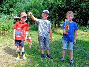 Timo, Nick und Ben-Luca (v.li.) präsentieren ihre aus Naturmaterialien gebastelten Wasserfilter. Foto: nh