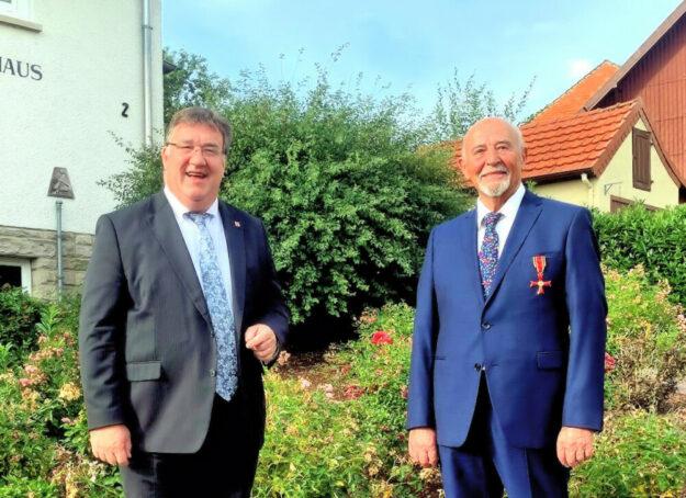 Konrad Kraß (re.) bekam am Ellenberger Bürgerhaus von Staatssekretär Mark Weinmeister das Bundesverdienstkreuz an die Brust geheftet. Foto: Staatskanzlei