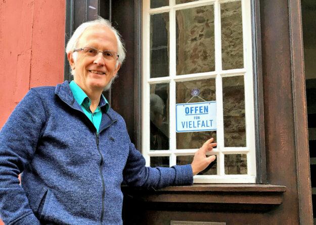 Dekan Christian Wachter zeigt, wo das Logo angebracht ist, das auf die Offenheit für Vielfalt hinweist. Foto: nh