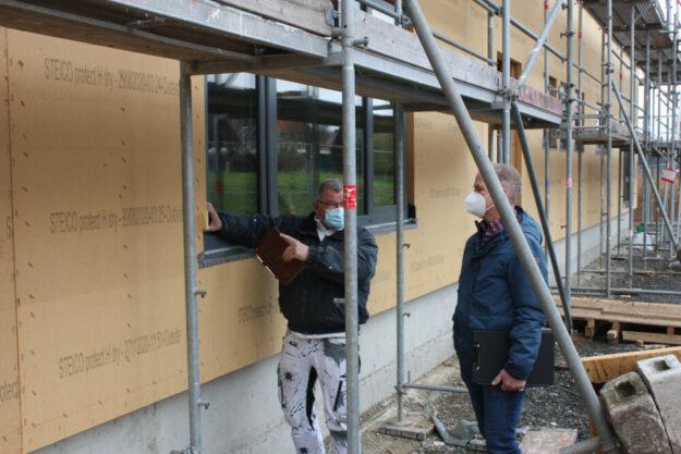 Auf der Außendämmung wird ein Fassadenputz aufgebracht. Rolf Sorokin, Inhaber des Malerbetriebs Weigand, und Klaus Arlt von der Bauverwaltung der Stadt Gudensberg besprechen die Ausführung. Foto: Stadt Gudensberg