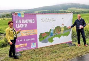 Rotkäppchen-Geschäftsführerin Heidrung Englisch und Niederaulas Bürgermeister Thomas Rohrbach präsentieren einen weiteren Cartoon der langen Ausstellung am Fulda-Radweg R1. Foto: Tourismusservice Rotkäppchenland