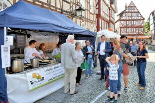 : Bürger*innen und der Magistrat mit Bürgermeister Dr. Nico Ritz (Mitte) freuen sich über das Angebot der Markt*Küche. Foto u. Text: Uwe Dittmer
