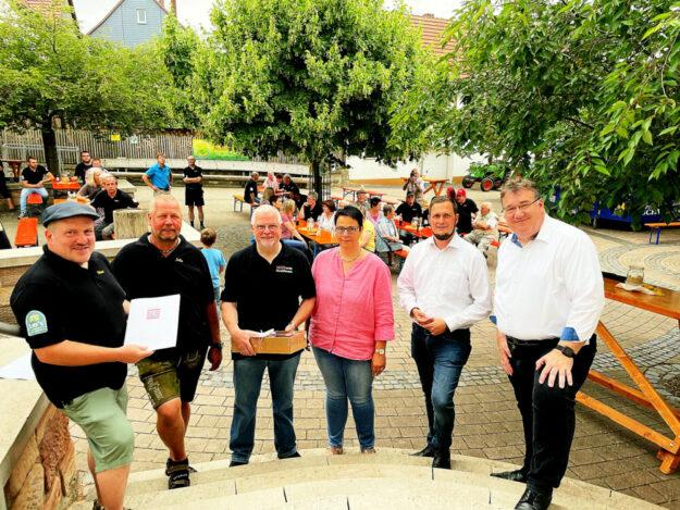 Schlepperfreunde (v.li.): Marc Richter, Jürgen Lau, Ortsvorsteher Martin Gombert, Helga Stumpf, Bürgermeister Heiko Manz, Mark Weinmeister. Foto: Hessische Staatskanzlei